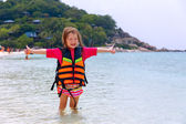 Little girl in a life jacket on the shores  — Stock Photo