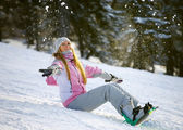 Happy smiling girl with lifted hands  on snowboard — Stock Photo