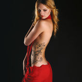 Beautiful girl in red dress back on black background — Stock Photo