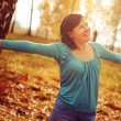 Young woman arms raised enjoying the fresh air in autumn forest — Stock Photo #69550451