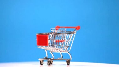 Shopping trolley on blue background — Stock Video