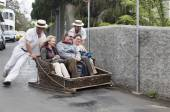 FUNCHAL, MADEIRA - MAY 20: Traditional downhill sledge trip on May 20, 2015 in Madeira, Portugal. Sledges were used as local transport. Currently these Toboggan riders are a touristic attraction — Stock Photo