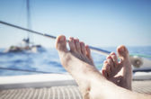 Man lounging on a catamaran sailboat trampoline with her feet propped up and crossed. — Stock Photo