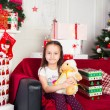 Little girl sitting on coach holding stuffed toy, Christmas gift, tray in the background — Stock Photo #64964849