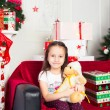 Little girl sitting on coach holding stuffed toy, Christmas gift, tray in the background — Stock Photo #64964875