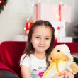 Little girl sitting on coach holding stuffed toy, Christmas gift, tray in the background — Stock Photo #64964889