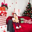 Little girl sitting on coach holding stuffed toy, Christmas gift, tray in the background — Stock Photo #64964919