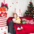 Little girl sitting on coach holding stuffed toy, Christmas gift, tray in the background — Stock Photo #64964933
