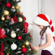 Little girl in  red cap hangs on the Christmas tree new year toys — Stock Photo #64965151