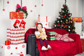 Little girl sitting on coach holding stuffed toy, Christmas gift, tray in the background — Stock Photo