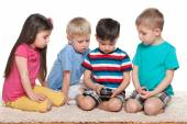 Four kids with a gadget on the carpet — Stock Photo