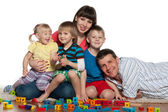 Family with children play the floor — Stock Photo