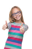 Preteen girl in a glasses with her thumbs up — Stock Photo