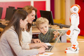Female teacher programming robot with children — Stock Photo