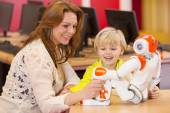 Female teacher programming robot with chil — Stock Photo