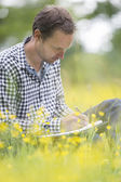 Environmentalist Writing On Notepad On Field — Stock Photo