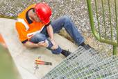 Worker Suffering From Leg Pain By Storage Tank Steps — Stock Photo