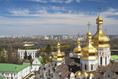 Kind to golden cupola of the Uspensky cathedral of the Kiev Pechersk Lavra in the foreground, the river Dnepr and Kiev on horizon. — Stock Photo