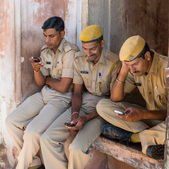 Amber Fort, India - September 27, 2014: three police security sitting at the entrance of Amber fort playing with their mobile phones — Stock Photo