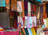 Colorful fabrics and shawls at a market stall — Stock Photo