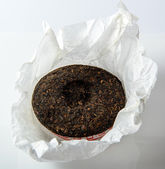 Chinese puer tea cake in unwrapped packing on white background — Stock Photo