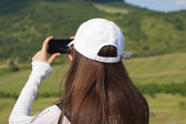 Brunette woman taking beautiful nature photo. — Stock Photo