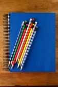 Colored Pencils and a notebook on a table — Stock Photo