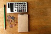 Notebook, calculator, pencil and coins — Stock Photo