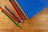 Colored Pencils and a notebook on a table — Stockfoto