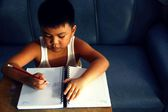 Young asian boy writing on a notebook — ストック写真