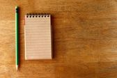 Pencil and a notebook on a table — Stockfoto