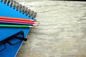 Notebook, eyeglasses and colorful pencils — Stock Photo