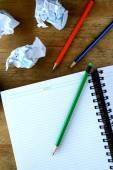 Notitieblok-, verfrommeld papier- en kleurrijke potloden — Stockfoto