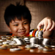 Young Boy Stacking or Piling Coins — Stock Photo #69984105