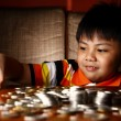 Young Boy Stacking or Piling Coins — Stock Photo #69984235