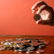 Hand picking a coin from a Bunch of loose change or coins — Stock Photo #71070407