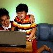 Two Young boys using a laptop computer and smiling — Stock Photo #74340763