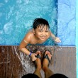 Young boy in a swimming pool and the feet of his parent — Stock Photo #75280187