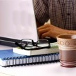 Coffee mug, stack of books and man working on a laptop computer in the background — Stock Photo #77175251
