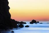 Sunrise on beach with rocks and sea — Stock Photo