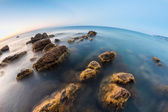 Underwater rocks at sunrise on beach — Stockfoto