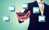 Businessman with email and cell phone — Stock Photo