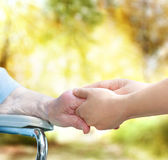 Senior lady in wheel chair holding hands with young caretaker — Stock Photo
