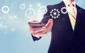 Businessman with gears over cellphone — Stok fotoğraf