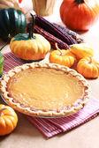 Pumpkin pie with autumn pumpkins and corn — Stock Photo