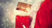 Santa Claus Opening a Red Christmas Present — Stock Photo