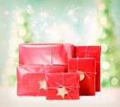 Gift boxes on christmas trees background — Stock Photo