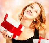 Happy young woman holding present boxes — Stock Photo