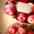 Red apples with a tag in a basket — Stock Photo #56597129