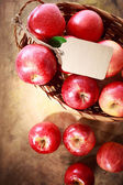 Red apples with a tag in a basket — Stock Photo